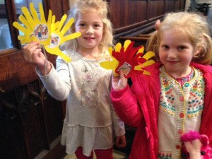 The children show the congregation their helping hands after learning about the tale of the Good Samaritan at a packed Sunday school on 15th November